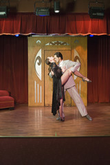 Hispanic couple performing tango on stage
