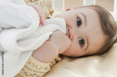 Mixed race baby girl laying in crib