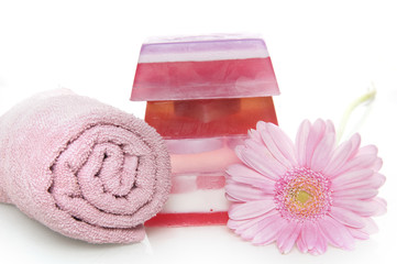 a flower, a towel and a pile of soap