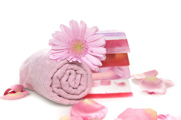 a towel, soap, a flower and rose leaves