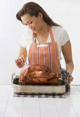 Hispanic woman basting turkey