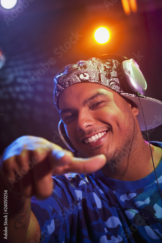 Hispanic dj in headphones pointing