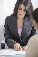 Hispanic businesswoman looking at job applicant's resume
