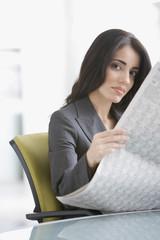 Hispanic businesswoman reading newspaper at desk