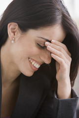 Hispanic businesswoman laughing with head in hands