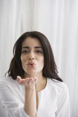 Hispanic woman blowing kisses
