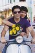 Hispanic couple riding scooter