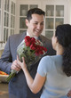 Hispanic man giving wife red roses