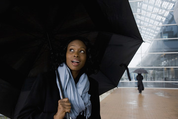 African businesswoman holding umbrella in rain