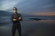 Hispanic woman in wetsuit on beach
