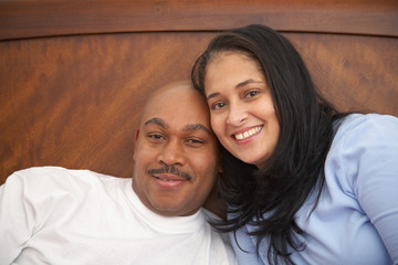 Antiguan man laying in bed with wife