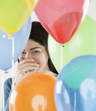 Hispanic woman laughing behind balloons