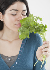 Hispanic woman smelling fresh cilantro
