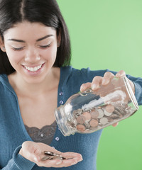 Hispanic woman pouring coins out of jar