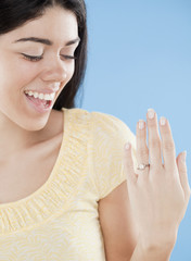Hispanic woman displaying engagement ring
