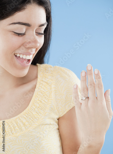 Hispanic woman displaying engagement ring