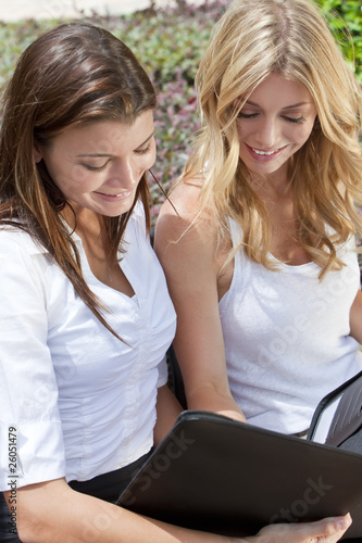 Two Young Businesswoman Outside Meeting Looking At Folder