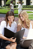 Two Young Businesswoman Outside Meeting With Laptop & Folder