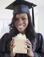 African woman in graduation cap and gown holding gift