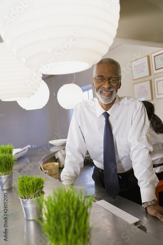 African business owner leaning on cafe counter