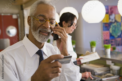 African business owner checking credit card over the telephone