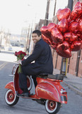 Mixed race man riding scooter with heart-shaped balloons
