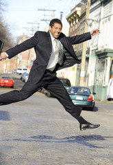 Mixed race businessman leaping across street