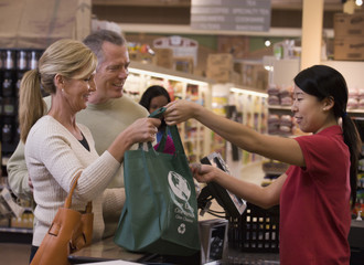 Mature woman using reusable bag in grocery store