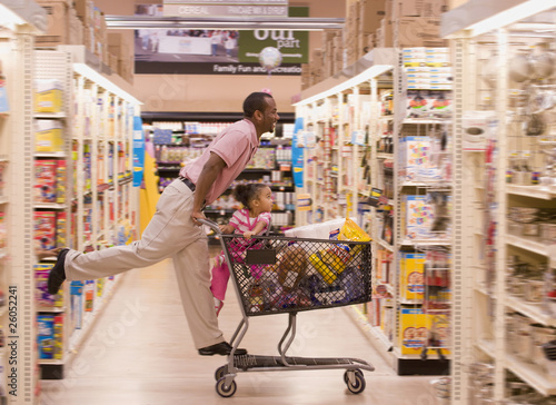 African father pushing daughter in grocery cart