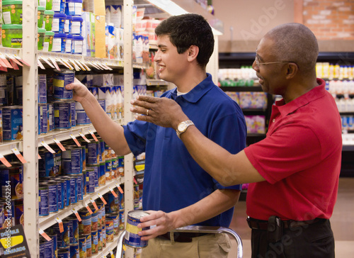 Manager working with stockist in grocery store