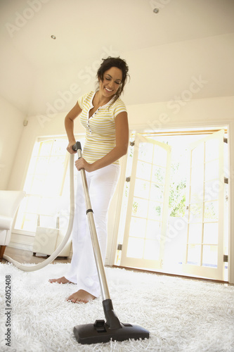Hispanic woman vacuuming floor