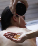 Masseuse pouring massage oil into hand