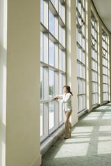 Hispanic businesswoman standing in office lobby