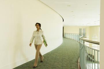Hispanic businesswoman walking in office corridor