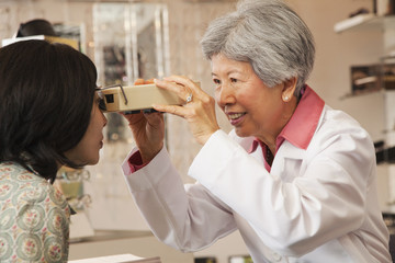 Chinese optician giving customer eye exam