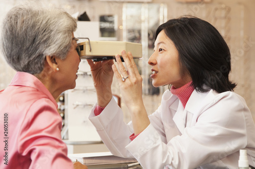 Korean optician giving woman eye exam