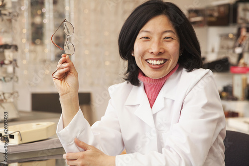 Korean optician holding eyeglasses