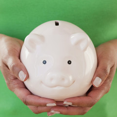 Close up of African woman holding piggy bank
