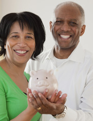 African couple holding piggy bank