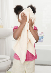 African girl drying face with towel