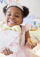 African girl eating cupcake and carrying gift