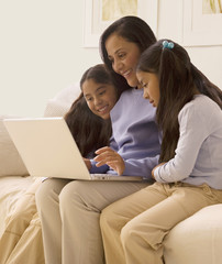African mother and daughters using laptop