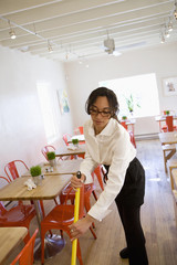 Mixed race woman mopping floor in cafe