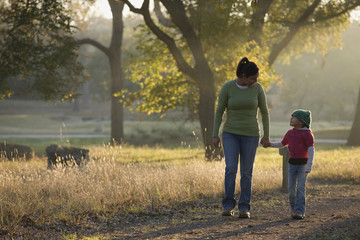 Hispanic mother walking with daughter in park