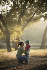 Hispanic mother comforting daughter in park
