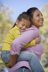 Hispanic woman giving daughter piggyback ride