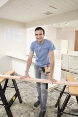 Hispanic man using sawhorse in kitchen