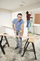 Hispanic man using sawhorse in kitchen