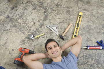 Hispanic man laying on floor with tools