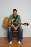 Mixed race man sitting with electric guitar
